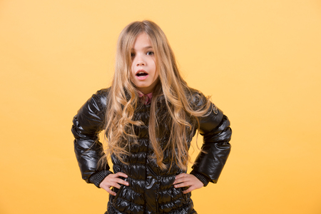 Girl child with surprised face and hands on hip with long blond hair in black jacket on orange background. Fashion, beauty, look, hairdresser concept Standard-Bild