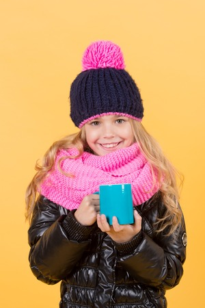Girl in hat, pink scarf, black jacket with mug. Tea or coffee break. Child with blue cup smile on orange background. Autumn season relax concept. Hot drink in cold weather. Banco de Imagens