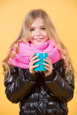 Tea or coffee break. Child hold mug in black jacket and pink scarf. Hot drink in cold weather. Autumn season relax concept. Girl with blue cup smile on orange background.