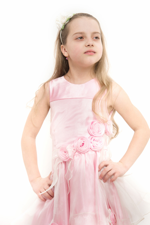 Fashion, look, beauty and style. Child in rosy dress pose isolated on white. Girl with flower accessory in long blond hair. Childhood, bloom, youth. Innocence, purity concept.