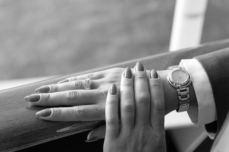 Female hands and wrist-watch with red manicure and golden ring on finger with diamonds near water Archivio Fotografico