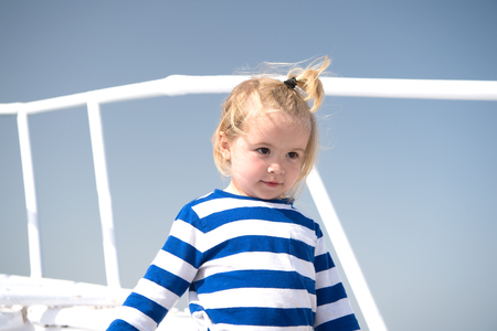 Boy in sailor shirt on blue sky. Child with blond hair on yacht on sunny day. Travel destination, cruise, travelling. Adventure, discovery, wanderlust. Summer vacation concept.
