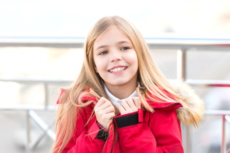 Adventure, discovery, journey. Girl with blond long hair smile outdoor. Child in red coat stand on bridge. Kid enjoy autumn day on blurred environment. Vacation, travelling concept.