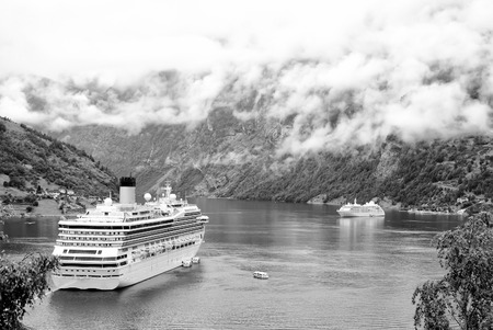Norway: cruiser ship or liner in fjord, bay or harbor, calm water surrounded by mountains on rocky sea shore covered with green trees on summer day on cloudy white sky Stok Fotoğraf