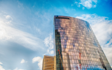 Tower building with reflection on glass facade walls on blue sky in district of la defense, paris, france. Architecture, structure, design. Business, commerce, future concept, copy space Banque d'images