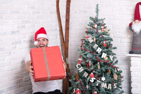 Gift giving and exchange concept. Man santa smile and give box at christmas tree. Holidays preparation and celebration. Happy boxing day. Macho in red hat with wrapped present. Stock Photo