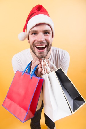 Man santa hold shopping bags on orange background. Macho shopper in xmas hat smile with paperbags. Winter sale concept. Christmas, new year presents. Happy holidays celebration.