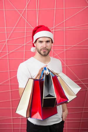 xmas sale concept. Macho shopper in red hat hold paperbags. Christmas, new year gift, present. Winter holidays celebration. Man santa with shopping bags on pink background. Stock Photo