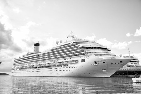 St. John, Antigua - March 05, 2016: beautiful large cruise ship, big white passenger boat, luxury modern Costa Magica vehicle at moorage in sea port, pier with people summer day on blue cloudy sky Editorial