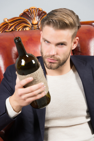 Man degustator with beard, stylish hair hold wine bottle on brown leather armchair. Wine tasting, degustation concept. Alcohol addiction, bad habits.