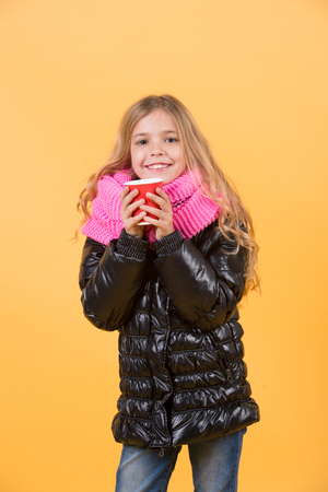 Autumn season concept. Girl with long blond hair in black jacket hold mug. Tea or coffee take away. Child smile with red cup on orange background. Warm up drink. Фото со стока
