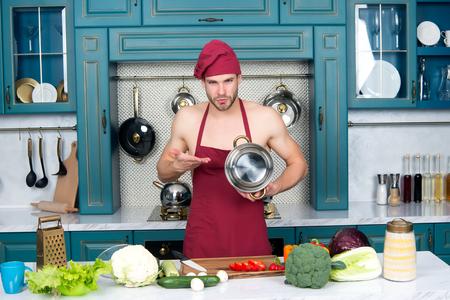 Mensenchef-kok in rode hoed, schort op naakt torsopunt bij steelpan bij keukenlijst. Eten, koken, voorbereiden. Productconcept presenteren