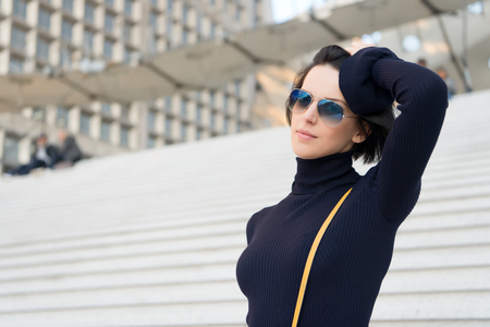 Look, beauty, style. Girl with brunette hair in black clothes. Ambition, challenge, success concept. Fashion and accessory. Woman in sunglasses on stairs. Parisian woman Stock Photo