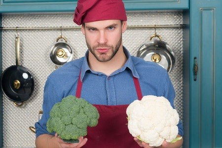 Man chef in red hat, apron hold cauliflower and broccoli vegetable in kitchen. Vegetarian, health, diet concept. Food, cooking, culinary, cuisine.