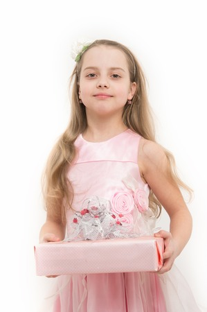 Child hold gift box isolated on white. Girl in pink dress with long blond hair. Holiday present and surprise. Birthday, anniversary celebration. Boxing day concept.