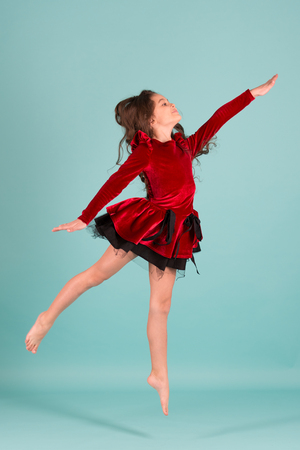 Girl dancer in red dress dance barefoot on blue background. Performance, ballet, activity, energy concept. Grace, beauty, fashion