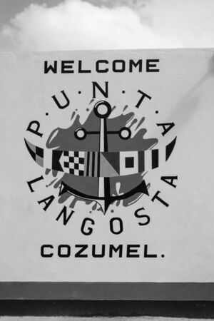 Cozumel, Mexico-December 24, 2015: welcome to cozumel text banner invitation with marine coat of arms painted on textured white wall outdoor Editorial