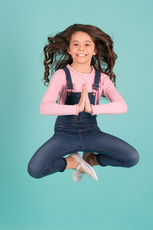 Girl in jeans overall jump in yoga pose on blue background. Meditation, concentration, zen concept. Fashion, beauty, look. Energy, energetic, activity, pilates, sport Stock Photo