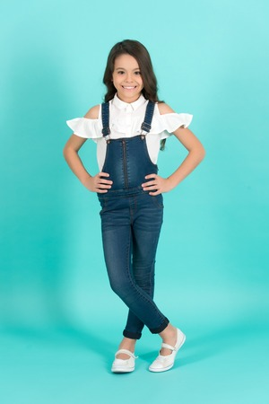 Child smile with long healthy brunette hair on blue background. Girl model pose in jeans overall full length. Beauty, look concept. Kid fashion, style. Youth, skincare, health. Stock Photo