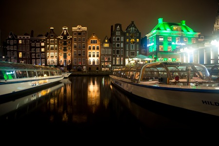 Amsterdam, Netherlands - October 01, 2017: tour boats on river channel and historical buildings by night. Water transport, transportation. Wanderlust, vacation, travel concept Editorial