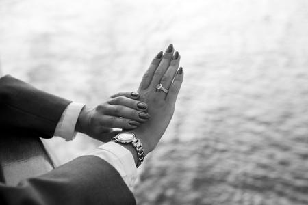 Mani femminili e orologio da polso con il manicure rosso e anello d'oro al dito con diamanti in prossimità di acqua Archivio Fotografico - 92642880