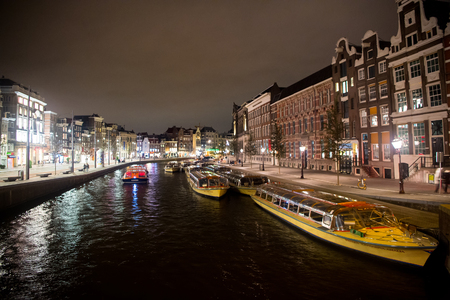 Amsterdam, Netherlands - October 01, 2017: water street with boats and historical buildings by night. River transport, transportation. Wanderlust, vacation, travel concept
