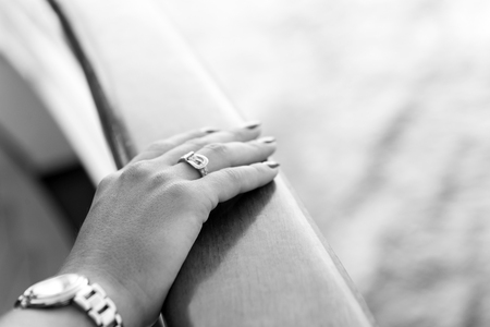 Female hands and wrist-watch with red manicure and golden ring on finger with diamonds near water Archivio Fotografico - 93547838