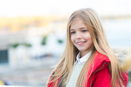 Happy childhood concept. Girl with blond long hair on autumn day outdoor. Kid fashion and style. Beauty, look, hairstyle. Child smile on blurred environment.
