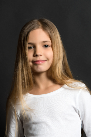 Youth, skincare, health. Girl with smile on cute face on dark background. Beauty, look, hairstyle. Happy child, childhood concept. Kid model smiling with long healthy hair.