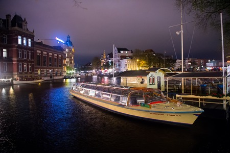 Amsterdam, Netherlands - October 01, 2017: boat on water canal and historical buildings by night. River transport, transportation. Wanderlust, vacation, travel concept