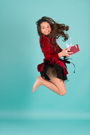 Happy child in red dress with present box jump barefoot on blue background. Boxing day concept. Birthday, new year, christmas, holidays celebration.