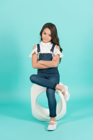 Kid fashion, style. Girl in jeans overall with folded hands on blue background. Youth, skincare, health. Beauty, look concept. Child model with long healthy brunette hair sit on chair.
