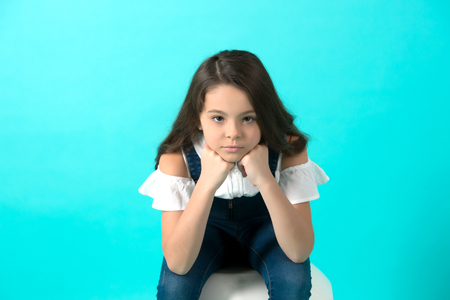 Girl prop chin on hands on blue background. Child with long brunette hair in jeans overall. Beauty, fashion, look, concept, copy space