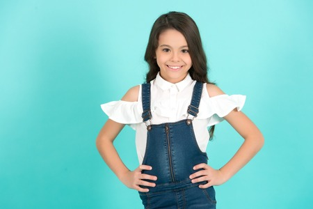 Kid girl smile in fashionable jeans overall with hands on hip on blue background. Fashion, beauty, style, look. Happy child, childhood concept.
