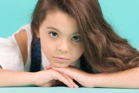Little girl with long brunette hair pose. Small model with adorable face skin on blue background. Skincare, beauty, look, hairstyle. Child, childhood, preteen, youth, punchy pastel Stock Photo