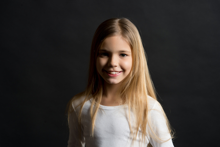 Beauty, look, hairstyle. Girl with smile on cute face on dark background. Happy child, childhood concept. Kid model smiling with long healthy hair. Youth, skincare, health.