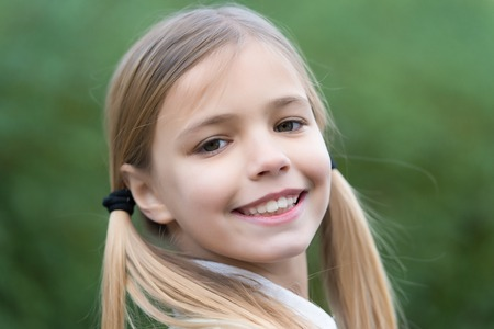 Little girl smile on natural background, childhood. Child with blond hair ponytails smiling outdoor. Happy childhood concept. Beauty, look, hairstyle.