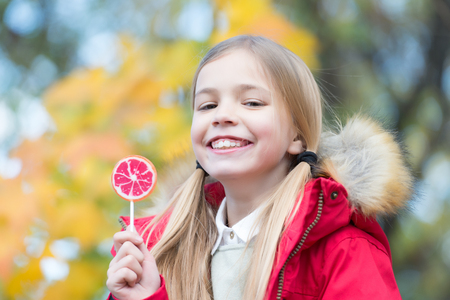 Girl smile with lollipop on natural background. Child smiling with candy on stick outdoor. Happy childhood concept. Food, dessert, snack. Punchy pastel trend Stock Photo