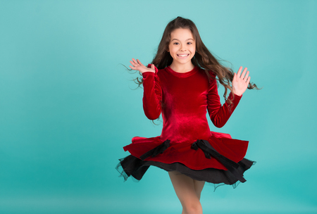 Girl dancer spin in red dress blue background. Happy child smile with long brunette hair. Performance, ballet, activity, energy concept. Grace, beauty, fashion, copy space