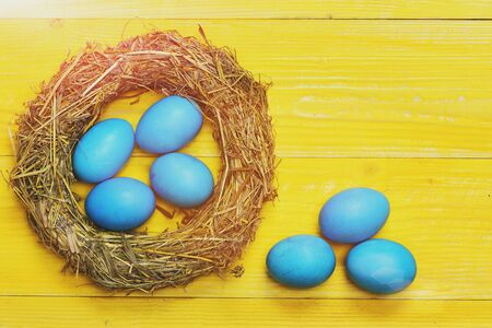 happy easter egg. holiday bunny and eggs, spring flower backround set of traditional eggs painted in blue color inside woven straw wreath on yellow vintage wooden background. Happy Easter concept