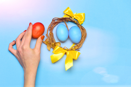 easter egg. funny holiday bunny rabbit and eggs wooden twig wreath with colorful handmade painted eggs and yellow ribbon in female hand of girl on blue background. Happy Easter concept Stock Photo