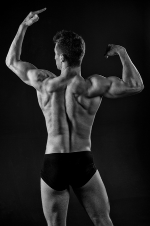 Power, health, wellness, bodycare. Man athlete with muscular body, torso, back view. Bodybuilder pose on dark background. Sportsman with strong hands, biceps, triceps, black and white, dieting Stock Photo