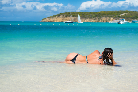 Sexy woman lie in transparent sea or ocean water in antigua under blue sky on idyllic sunny day. Summer vacation on caribbean. Recreation, sunbathing, bathing concept