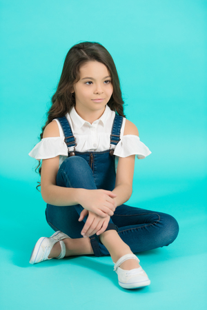 Child model in jeans overall sit on floor. Girl with long brunette hair on blue background. Fashion, style concept. Beauty, look, hairstyle. Childhood, preteen, youth, punchy pastel Stock Photo