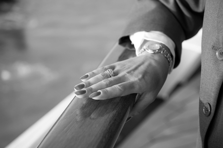 Female hands and wrist-watch with red manicure and golden ring on finger with diamonds near water Archivio Fotografico - 96001675