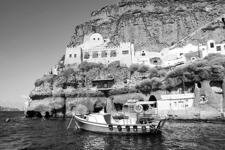 Santorini, Greece - JULY 15, 2017: sailing boat in bay of Santorini island on water near building on mountain