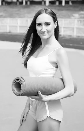 Fitness Girl with Yoga Mat Standing Outdoor in Nature - Fit woman with exercise accessory at stadium. sport and fitness concept