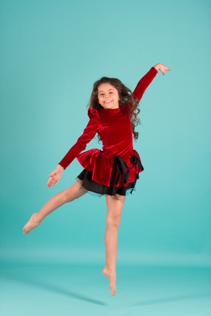 Child dance in red dress barefoot. Little girl dancer jump on blue background. Happy childhood concept. Performance, ballet, gymnastics, activity, energy. Grace, beauty, fashion. Punchy pastel trend.
