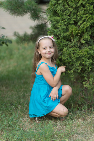 Little girl pose at green bush on grass, beauty. Happy child smile in summer park, childhood. Kid fashion, beauty, look, hair, hairstyle. Banque d'images