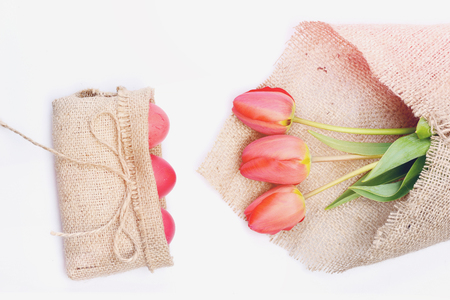 hapyy easter holidays eggs and bunny Bunch of flowers near pink Easter eggs in rustic sackcloth bag with bow.